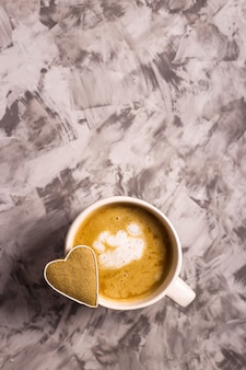 Selbst gemachter lebkuchenplätzchen in form eines herzens auf einer cappuccinoschale