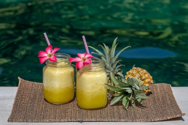 Selbst gemachter mango-ananas-smoothie mit kokosmilch in zwei glasbechern in der nähe des pools