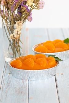 Selbst gemachter orange kuchen auf hölzerner weinlesetabelle