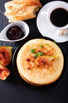Selbst gemachter organischer pfannkuchenstapel mit feigenfrühstück auf schwarzem