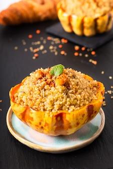 Selbst gemachter organischer Quinoa des gesunden Lebensmittels angefüllter süßer Mehlkloßkürbis auf schwarzem Schieferstein