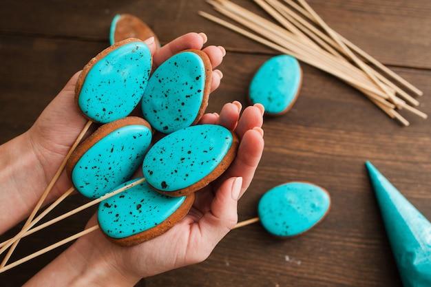 Selbst gemachter osterkuchen knallt mit blauem zuckerguss auf rustikaler hölzerner tischoberansicht