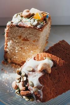 Selbst gemachter ostern-kuchen verziert mit zuckerglasur, nüssen, kandierten früchten