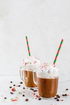 Selbst gemachter pfefferminz-mokka, weihnachtskaffeegetränk mit zuckerstangen, schlagsahne und minzensirup, auf weißer marmortabelle
