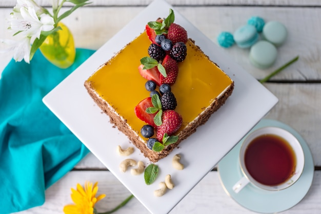 Selbst gemachter quadratischer kuchen verziert auf gelbem gelee und beeren mit minze auf hellem hintergrund.