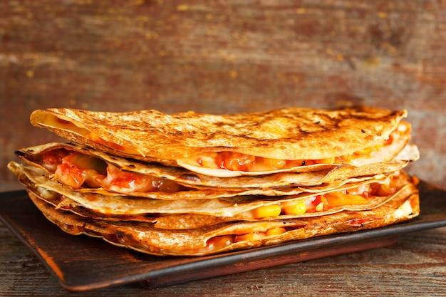 Selbst gemachter quesadilla auf einer platte auf einem holztisch