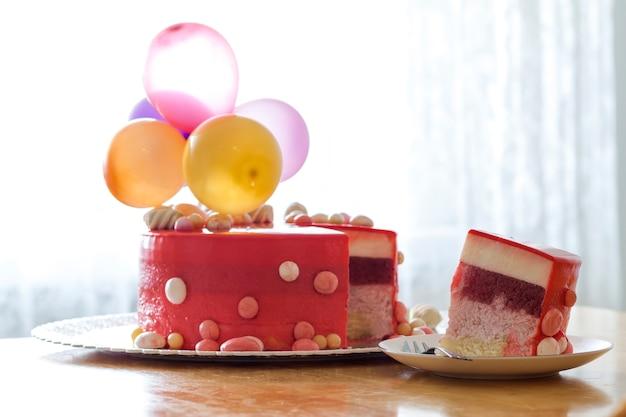 Selbst gemachter roter geburtstagskuchen mit luft baloons. scheibe eines roten samtkuchens auf einer platte.