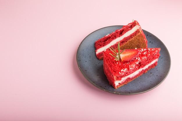 Selbst gemachter roter samtkuchen mit milchcreme und erdbeere auf blauer keramikplatte lokalisiert auf einem rosa pastellhintergrund. seitenansicht, kopierraum.
