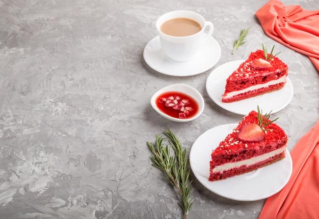Selbst gemachter roter samtkuchen mit milchcreme und erdbeere mit tasse kaffee auf einer grauen betonoberfläche. seitenansicht, kopierraum.