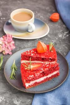 Selbst gemachter roter samtkuchen mit milchcreme und erdbeere mit tasse kaffee auf einer schwarzen betonoberfläche. seitenansicht, selektiver fokus.