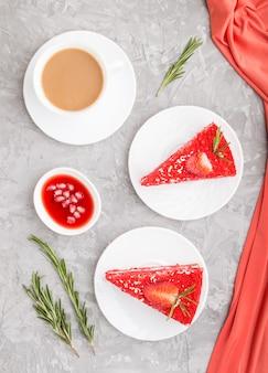 Selbst gemachter roter samtkuchen mit milchcreme und erdbeere mit tasse kaffee auf grauem betonhintergrund. draufsicht, nahaufnahme.