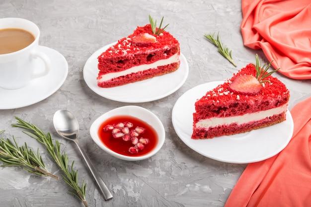Selbst gemachter roter samtkuchen mit milchcreme und erdbeere mit tasse kaffee auf grauem betonhintergrund. seitenansicht.