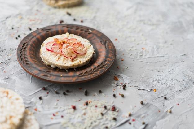 Selbst gemachter runder puffreiskuchen garniert mit rübenscheiben und käse