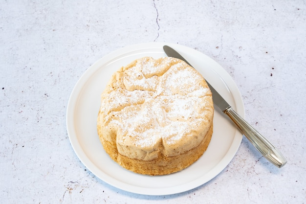 Selbst gemachter savoie-kuchen auf einer hübschen weißen porzellanschale mit marmelade in einem glas