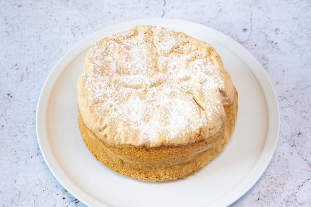 Selbst gemachter savoie-kuchen auf einer hübschen weißen porzellanschale