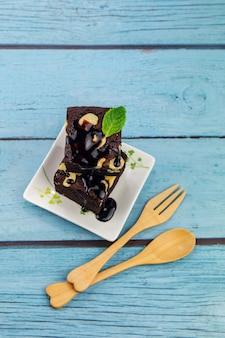 Selbst gemachter schokoladen-brownie auf einem blauen hölzernen hintergrund mit holzbesteck