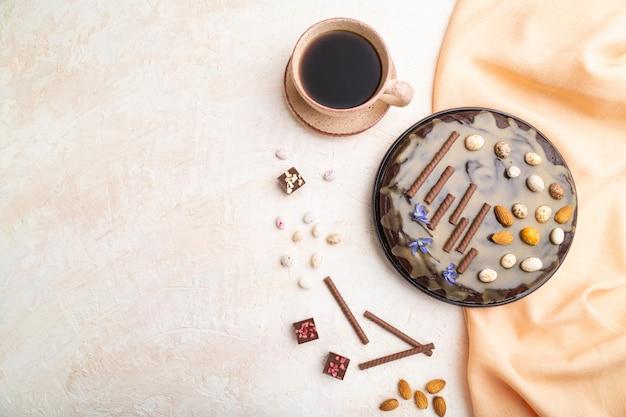 Selbst gemachter schokoladen-brownie-kuchen mit karamellcreme und mandeln mit tasse kaffee auf weißem betonhintergrund.