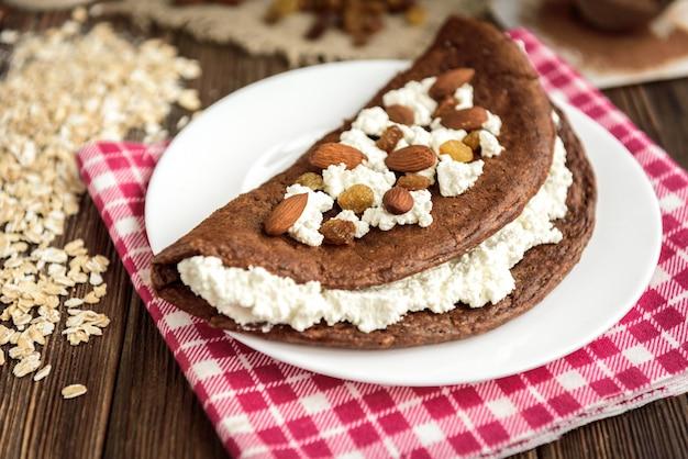 Selbst gemachter schokoladen-hafer-pfannkuchen mit hüttenkäse auf weißem teller auf dunklem holztisch.