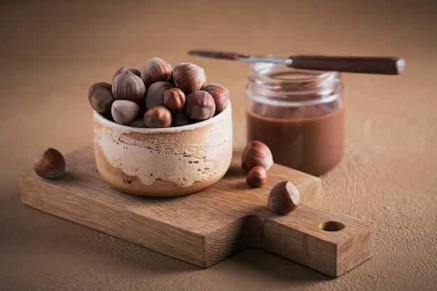 Selbst gemachter schokoladen-haselnuss-milchaufstrich auf einer braunen oberfläche