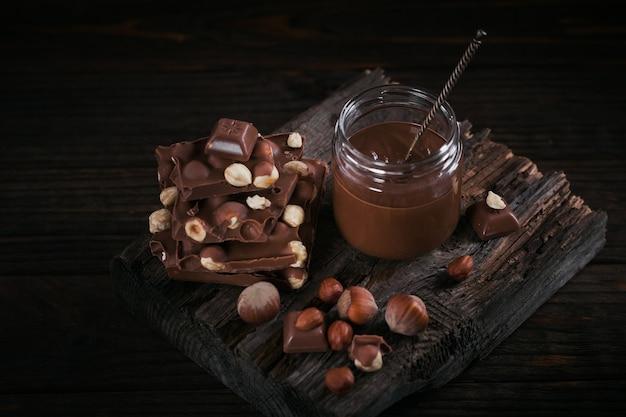 Selbst gemachter schokoladen-haselnuss-milchaufstrich auf glas auf dunkler holzoberfläche