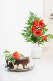 Selbst gemachter schokoladenkuchen mit erdnussbuttercremeschichten, die mit mohnblumen über einem weißen schreibtisch verziert werden. seitenansicht.