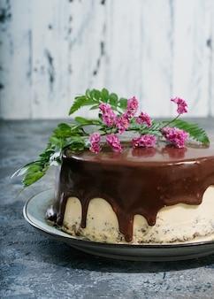 Selbst gemachter schokoladenkuchen mit erdnussbuttercremeschichten verziert mit blumen auf der oberseite über einem dunklen rustikalen schreibtisch. seitenansicht.