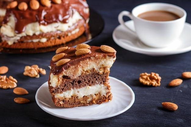 Selbst gemachter schokoladenkuchen mit milchcreme, karamell und mandeln auf schwarzem hölzernem hintergrund. tasse kaffee.