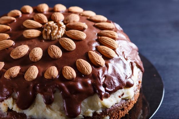 Selbst gemachter schokoladenkuchen mit milchcreme und mandeln auf schwarzem hölzernem hintergrund.