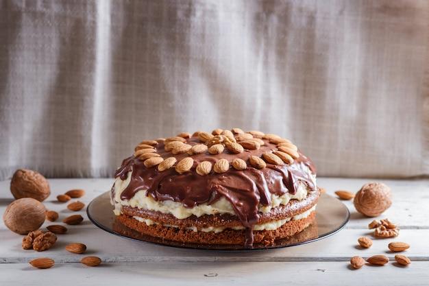 Selbst gemachter schokoladenkuchen mit milchcreme und mandeln auf weißem holztisch.
