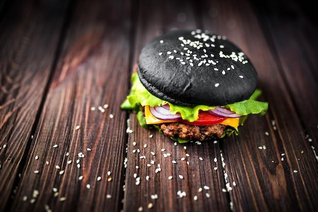 Selbst gemachter schwarzer burger mit käse. cheeseburger mit schwarzem brötchen o