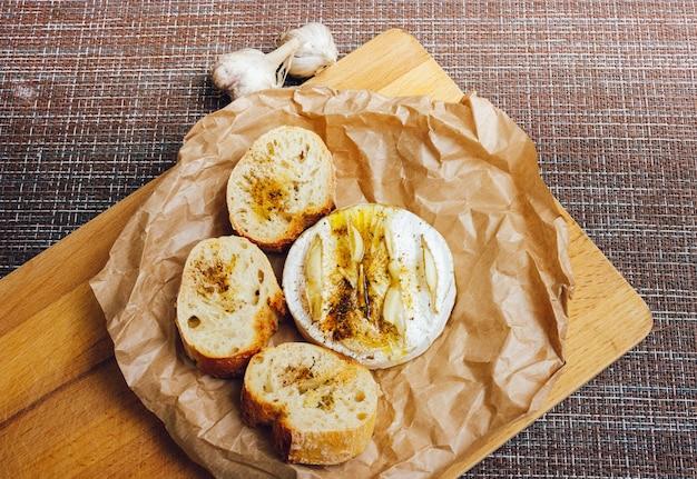 Selbst gemachter selbstgebackener camembert mit knoblauch. käse mit weißem schimmel. gebackener käse.