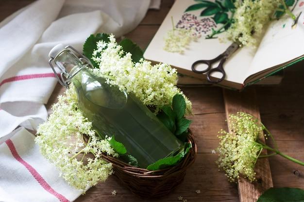 Selbst gemachter sirup von holunderblüten in einem glas und holunderzweigen auf einem holztisch rustikaler stil.