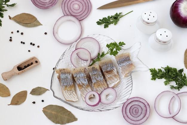 Selbst gemachter snack vom gesalzenen hering mit roter zwiebel und senf auf weißem hintergrund, ansicht von oben