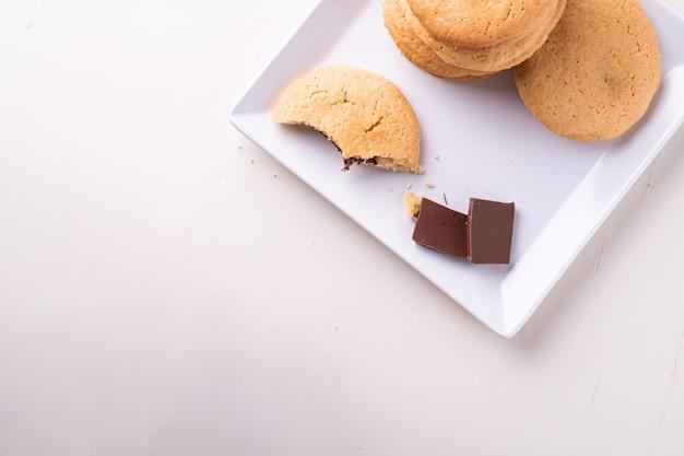 Selbst gemachter stapel von shortbread-schokoladenplätzchen mit einem gebissenen keks und zwei schokoladenstücken auf der weißen tischplatte des weißen tellers
