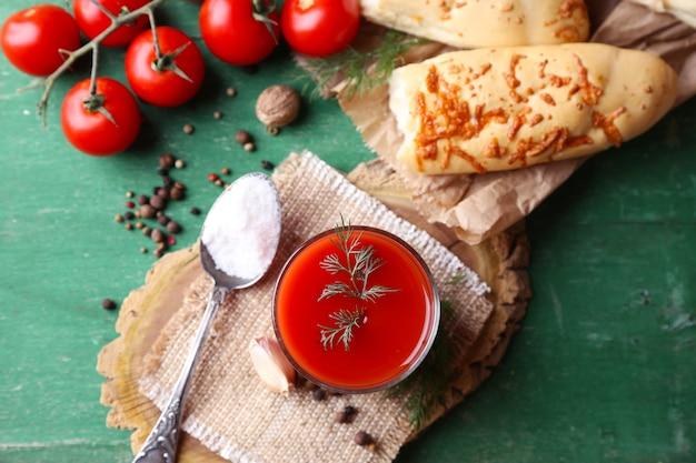 Selbst gemachter tomatensaft im glas, in den gewürzen und in den frischen tomaten auf hölzernem hintergrund