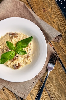 Selbst gemachter traditioneller italienischer pilz risotto auf holztisch