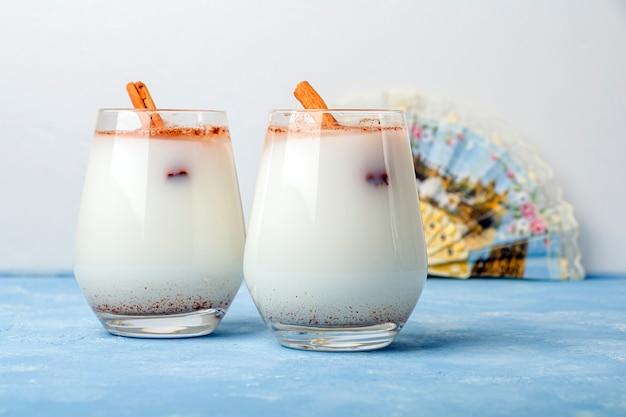 Selbst gemachter traditioneller mexikanischer reis horchata in einem glas und maracas auf blauem hintergrund. frisches kühles getränk oder cocktail aus reis, vanille und zimt oder mandel. cinco de mayo hintergrund
