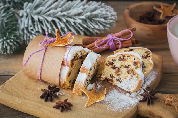 Selbst gemachter traditioneller weihnachtsdessertstollen mit getrockneten beeren, nüssen und puderzucker oben steht auf rustikalem holztisch