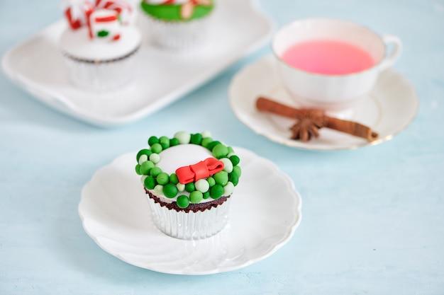 Selbst gemachter weihnachtscupcake mit traditionellen rotgrünen dekorativen symbolelementen
