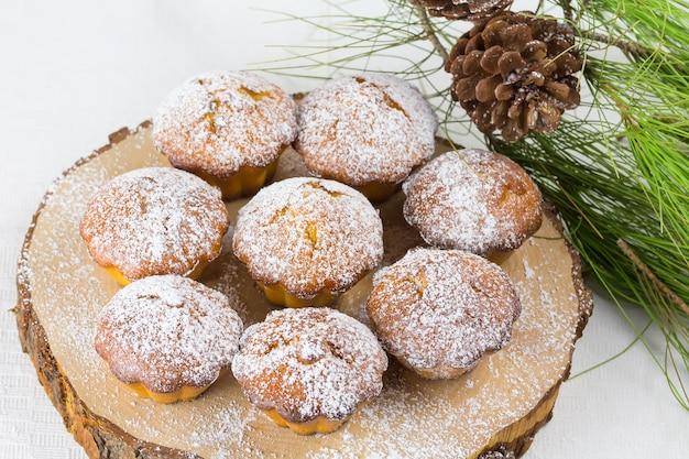 Selbst gemachter weihnachtskleiner kuchen, weihnachtsmuffins und dekoration des neuen jahres und kiefernniederlassungen und -kegel