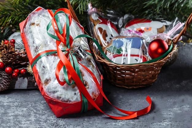 Selbst gemachter weihnachtskuchen verziert mit lebkuchenplätzchen in einem neujahrs-gefolge auf einer dunkelheit