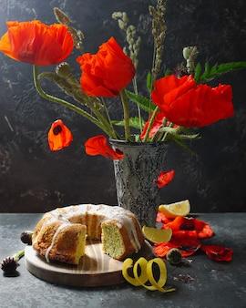 Selbst gemachter zitrone gebundener kuchen und rote mohnblumenblumen im weinlesevase. fliegende blütenblätter