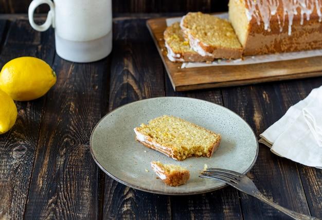 Selbst gemachter zitronenkuchen auf einem holztisch. rezept. gebäck.
