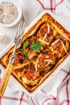 Selbst gemachtes abendessen der gesunden diät, zubereitete hühnertruthahnfleischklöschen mit soße, käse, grüns. auf einem weißen marmortisch mit gewürzen.