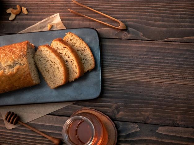 Selbst gemachtes bananenbrotpfund geschnitten mit acajounüssen und honig auf holztisch.