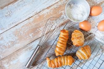 Selbst gemachtes Brot mit Ei und Schüssel Mehl auf hölzernem hinterem Boden