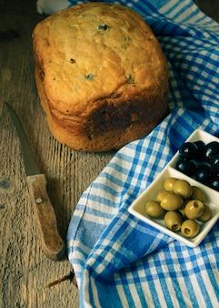 Selbst gemachtes brot mit oliven auf altem holztisch