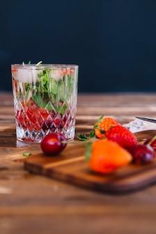 Selbst gemachtes erdbeercocktail im glas auf hölzernem schreibtisch