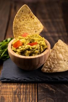 Selbst gemachtes frisches guacamole und chips essfertig. gesundes und vegetarisches essen.