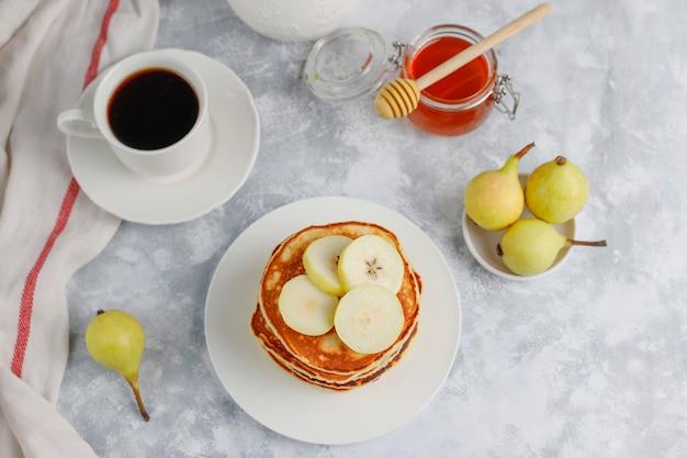 Selbst gemachtes frühstück: pfannkuchen im amerikanischen stil, serviert mit birnen und honig bei einer tasse tee auf beton. draufsicht und kopie